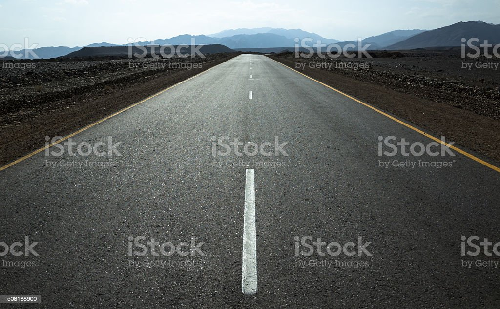 Middle of the road: desert highway and distant mountains. stock photo