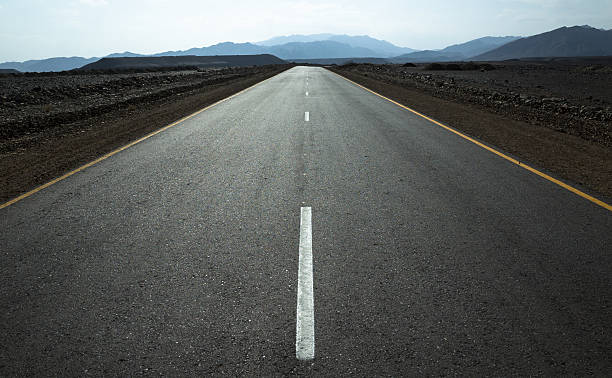Middle of the road: desert highway and distant mountains. Afar region, Ethiopia. middle of the road stock pictures, royalty-free photos & images
