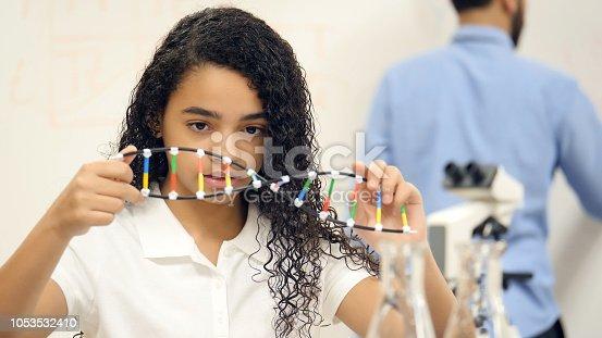 istock Middle school girl examines DNA helix model 1053532410