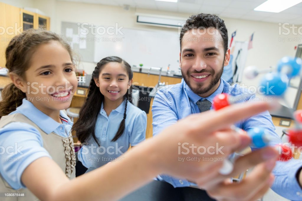 Young male middle school science teacher teaches students about...