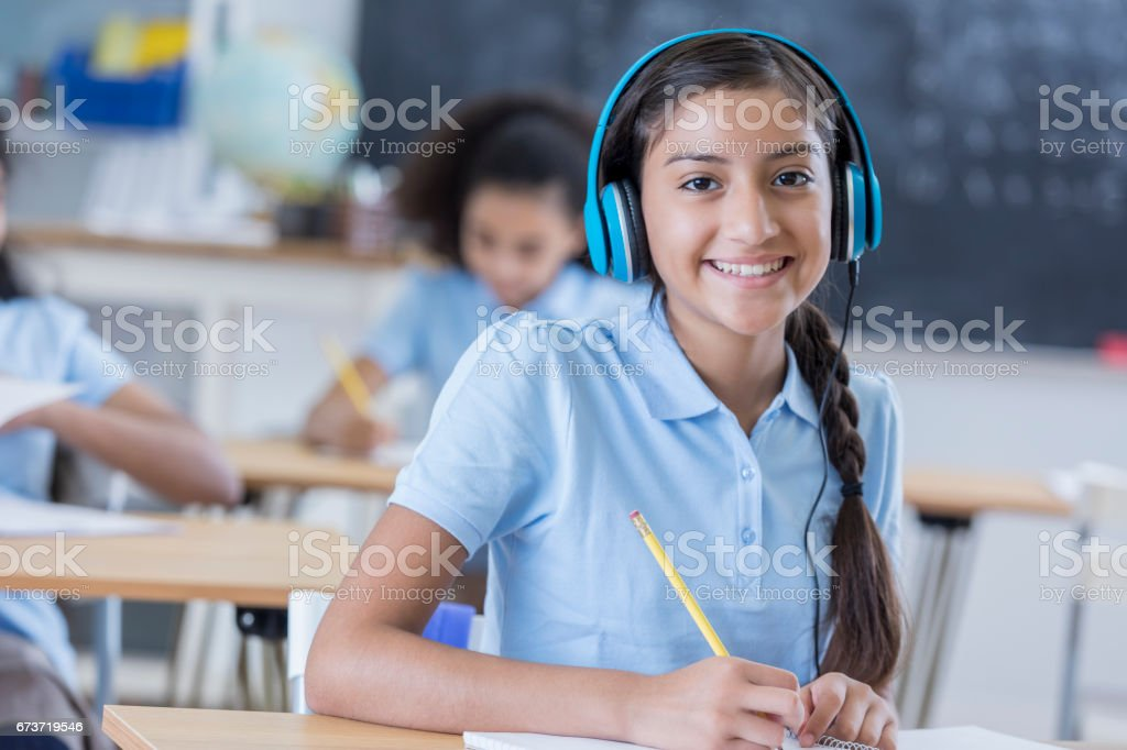 Middle school student listens to headphones during class stock photo