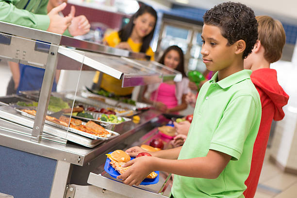 Middle school students getting lunch items in cafeteria line stock photo