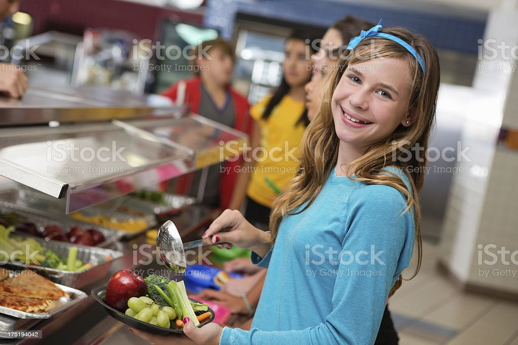 Middle school students making healthy choices in cafeteria lunch line royalty-free stock photo