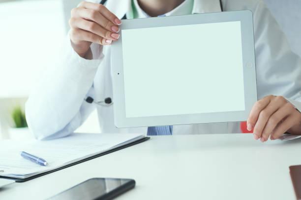 Mittlerer Abschnitt der weiblichen Medizin Arzt zeigt Tablet-Computer mit weißem Bildschirm. Kontaktinformationsaustausch, Einführung der Geste beim offiziellen Sitzungskonzept – Foto