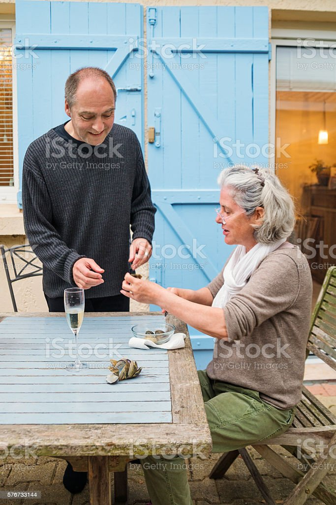 Middle-age couple couple eating oysters outdoors for apero. – Foto