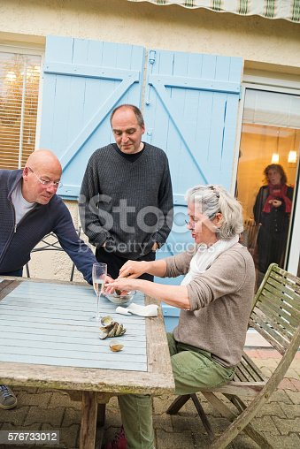 Middle-age woman with white hair is opening oysters outdoors for apero. Two man standing beside her are eating them. A woman inside the house is coming out. A white wine glass is on the table.  Vertical waist up shot with copy space. This was taken in France.