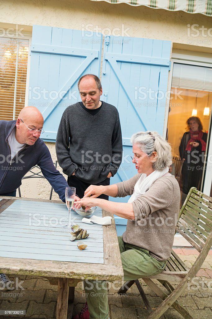 Middle-age friends eating oysters outdoors for apero. – Foto