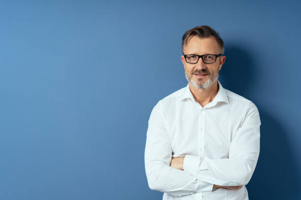 Middle-age man in glasses with arms folded stock photo