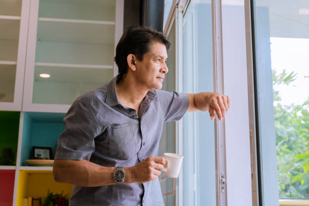 Middle-aged Asian man looking through a window, sipping coffee and using ideas Middle-aged Asian man looking through a window, sipping coffee and using ideas ziek stock pictures, royalty-free photos & images