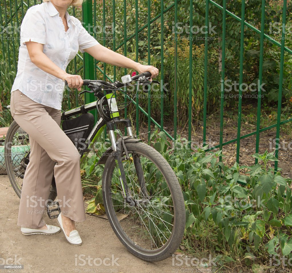 Middle-aged attractive blond woman on a Bicycle in the royalty-free stock photo