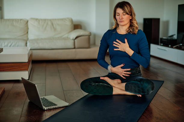 Middle-aged brunette sitting in lotus poses and meditating at home while following video tutorials. stock photo