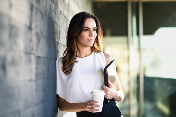 Middle-aged businesswoman taking a coffee break in an office building. stock photo