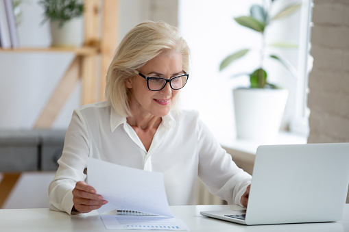 Aged businesswoman typing on pc holds paper prepare report analyzing work results feel satisfied do paperwork use business app online software for data analysis, financier manage firm finances concept