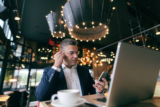 middle-aged caucasian man with serious face dressed smart casual using smart phone for call while sitting in cafe. in the desk laptop and coffee. - owner laptop smartphone foto e immagini stock
