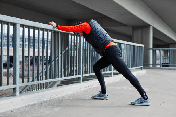 Middle-aged caucasian sportsman doing warm up excises outdoors before running. stock photo