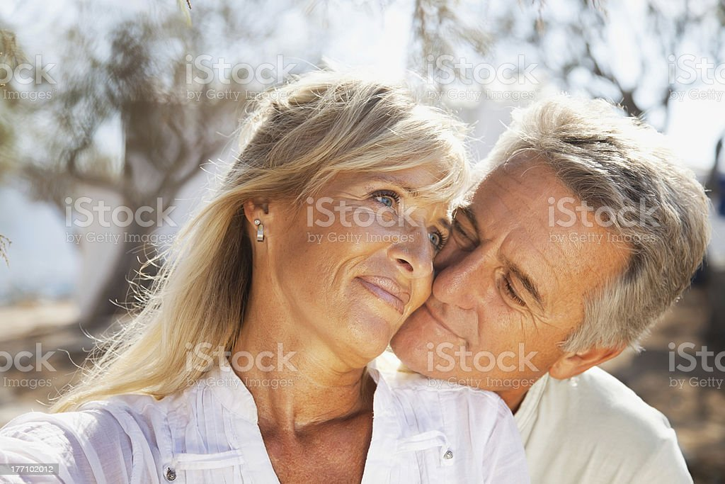Middle-aged couple embracing outdoors on a warm day royalty-free stock photo