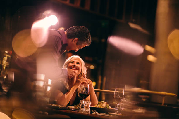 Middle-aged couple flirting on dinner date night at gourmet restaurant Romantic mature couple in love celebrating anniversary and flirting while having dinner at luxurious restaurant date night romance stock pictures, royalty-free photos & images