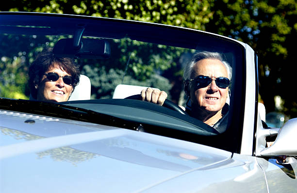 Middle-aged couple in a convertible with sunglasses on stock photo