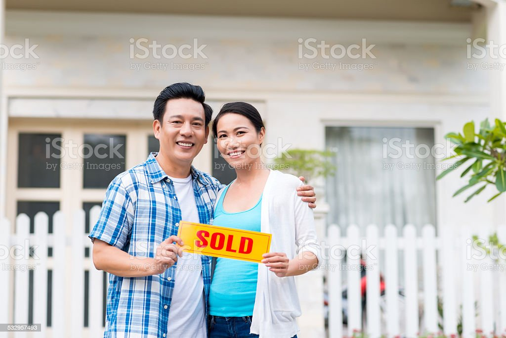 Middle-aged couple with sold sign stock photo