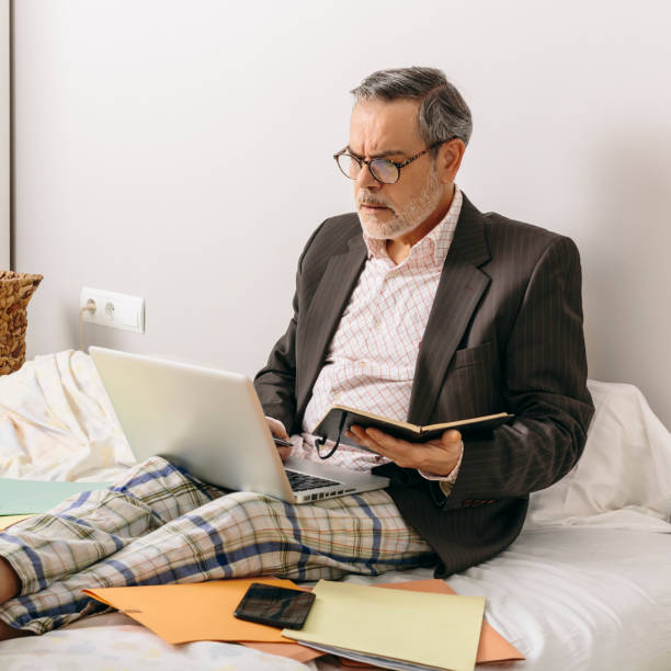Middle-aged executive attending a business meeting via videoconference from the office mounted on his home bed stock photo