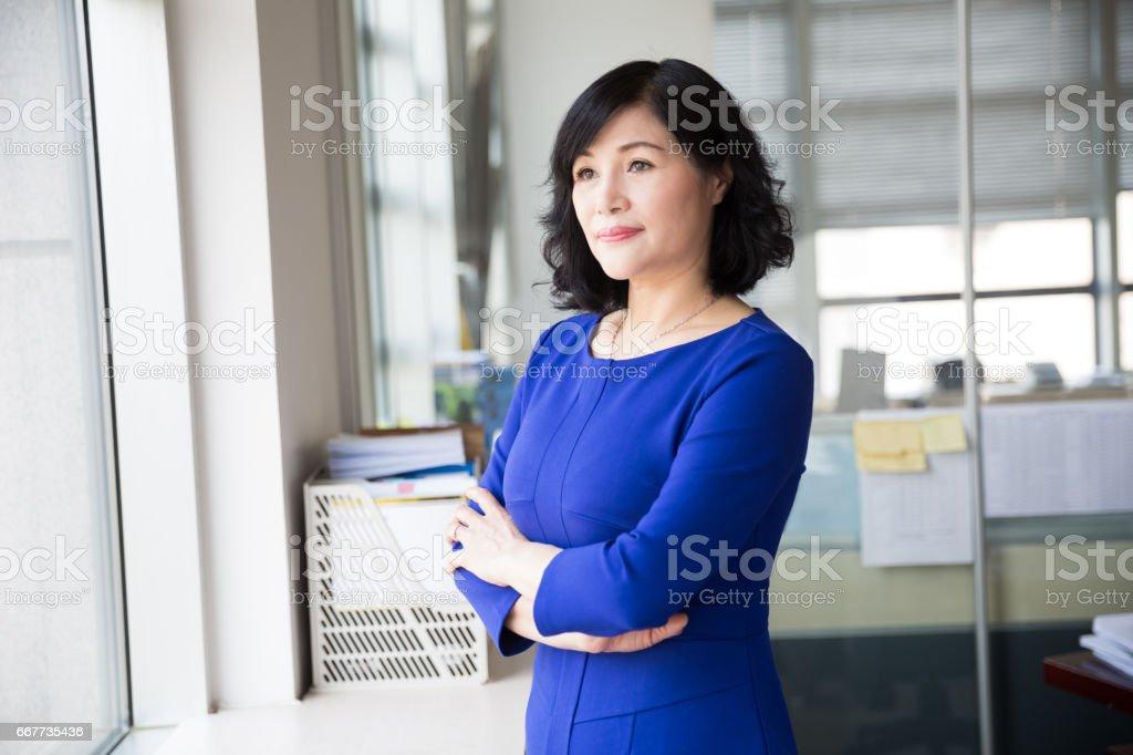 mittleren Alters Managerin posiert in der Nähe von Fenster – Foto