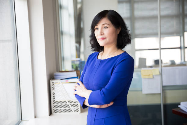 middle-aged female manager posing near by window mature, middle-aged woman is a successful business person civil servant stock pictures, royalty-free photos & images