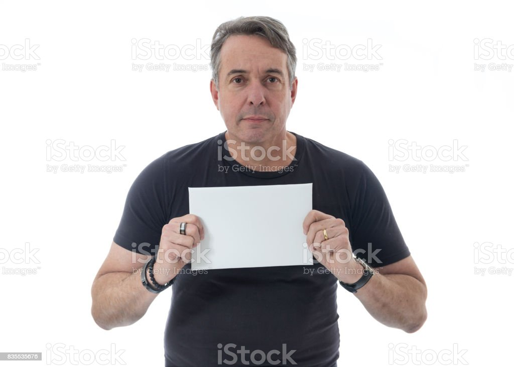 Middle-aged gray-haired man is wearing a black T-shirt. Isolated on white background. He is serious and holds with both hands a blank billboard. stock photo
