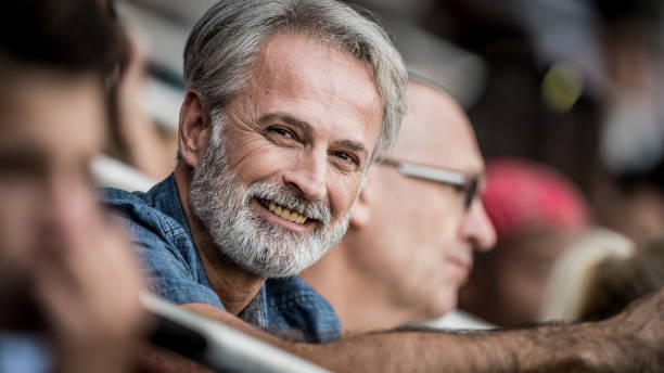 middle-aged gray-haired man smiling and looking at camera - soccer supporter portrait imagens e fotografias de stock