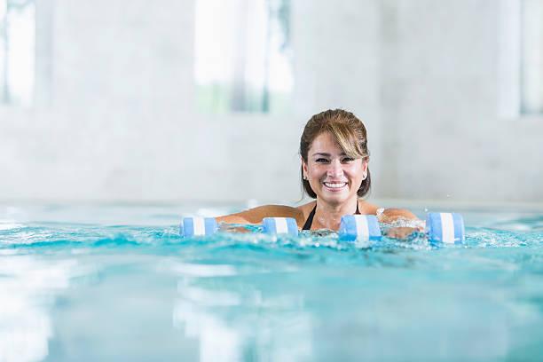 Medio invecchiato donna ispanica facendo acqua aerobica - foto stock