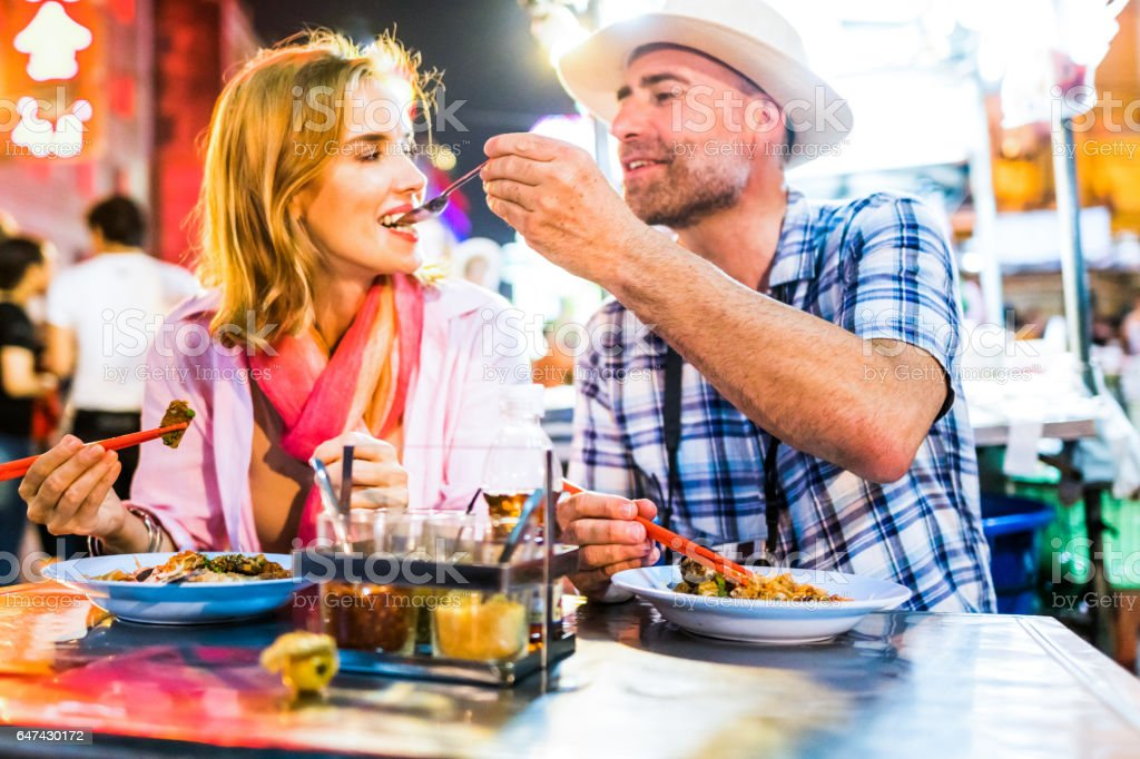 Middle-aged man and his companion handsome blond lady in Bangkok Chinatown stock photo
