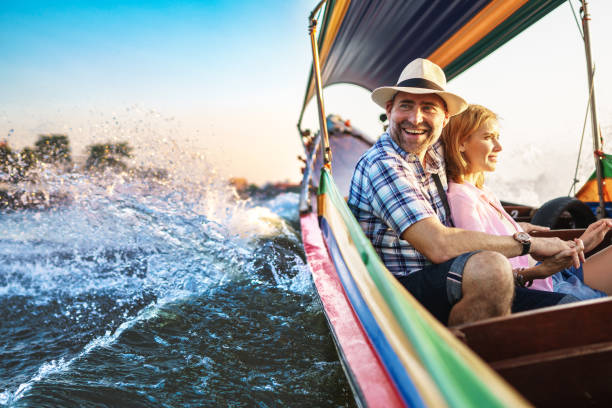 middle-aged man and his companion handsome blond lady on a boat ride in bangkok - enjoying wealthy life imagens e fotografias de stock