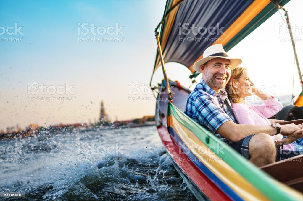 Middle-aged man and his companion handsome blond lady on a boat ride in Bangkok stock photo
