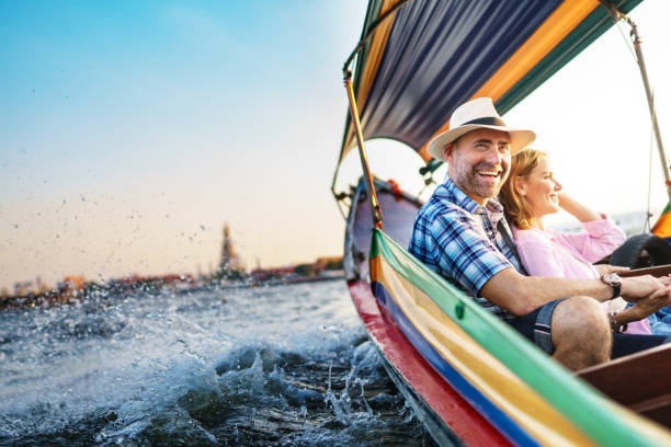 middle-aged man and his companion handsome blond lady on a boat ride in bangkok - recreational pursuit stock pictures, royalty-free photos & images