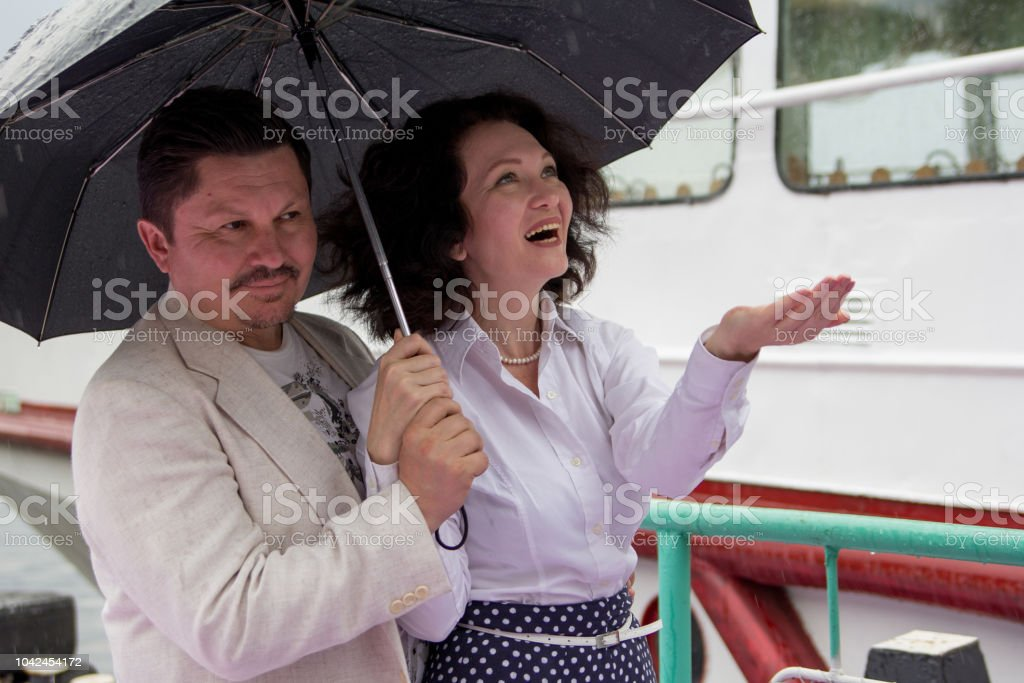Middle-aged man and woman smile under the umbrella during the rain....