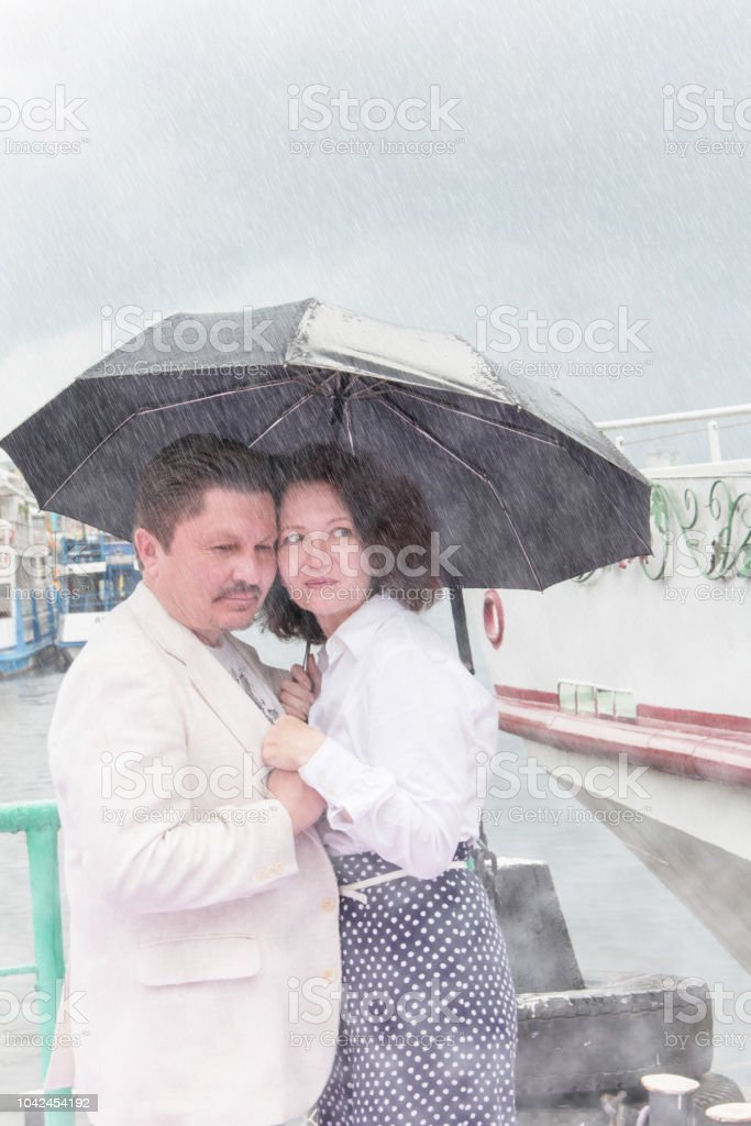 Sensual middle-aged couple in summer in the rain. Middle-aged man and...