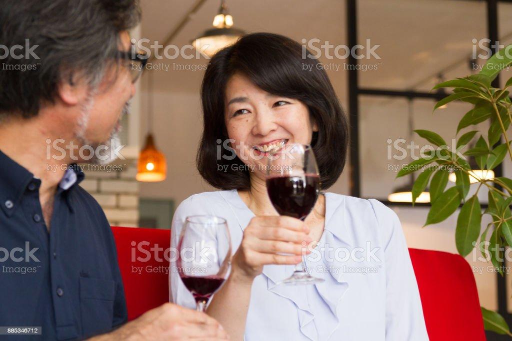 Im Mittleren Alter Mann Und Frau Im Gesprach Auf Sofa Trinken Wein