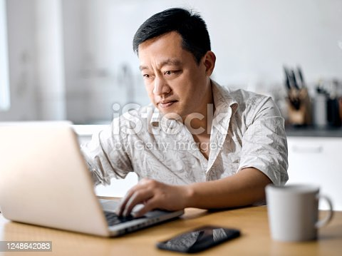 Middle-aged man freelancer using laptop studying online working from home, happy casual millennial guy typing on pc notebook surfing internet looking at screen enjoying distant job sit at table