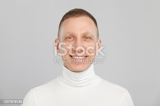 middle-aged man headshot in a white turtleneck.