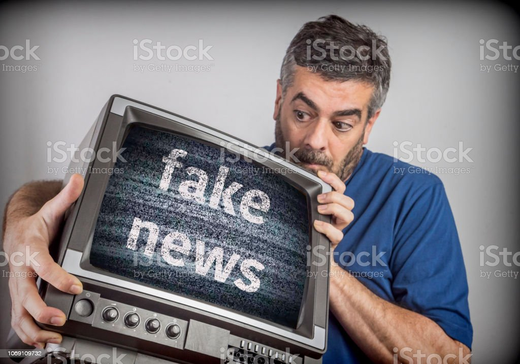 Middle-aged man holds a TV with fake news screen, conceptual image – zdjęcie