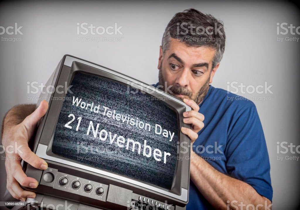 Middle-aged man holds a TV with World Television Day 21 November screen, conceptual image – zdjęcie