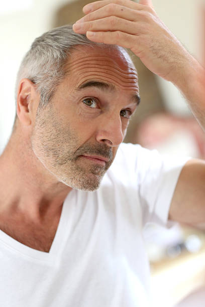 Middle-aged man in bathroom looking at hair loss stock photo