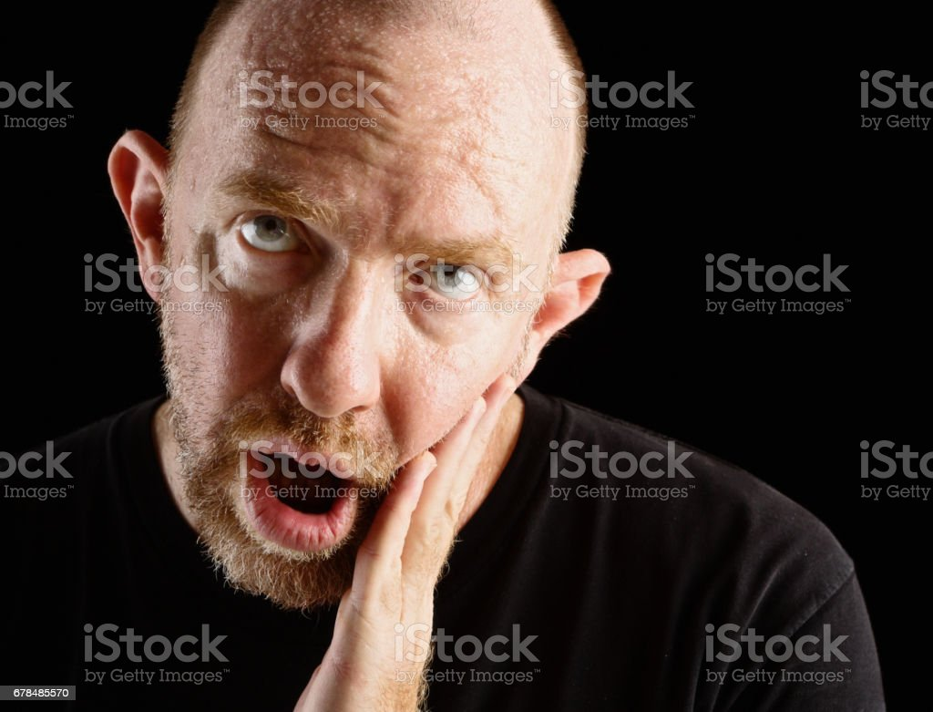 A middle-aged man is slack-jawed and vacant looking, possibly brain damaged stock photo