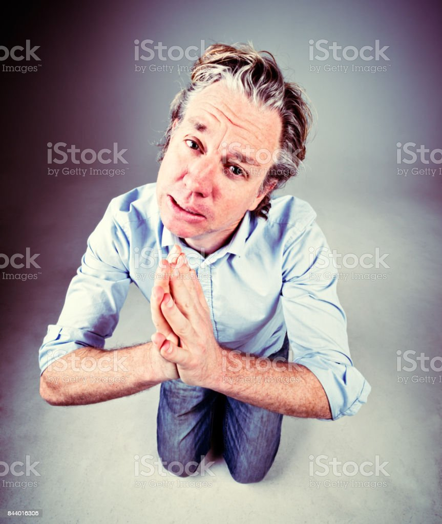 Middle-aged man kneels, hands folded, pleading pitifully stock photo
