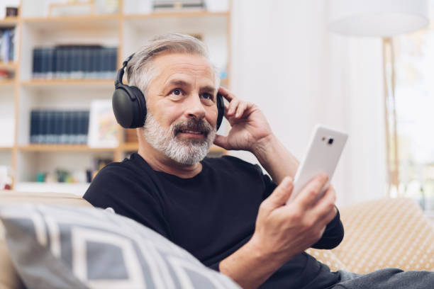 Middle-aged man listening to music online at home Portrait of a middle-aged man using his mobile phone for listening to music online through modern headphones at home listening stock pictures, royalty-free photos & images