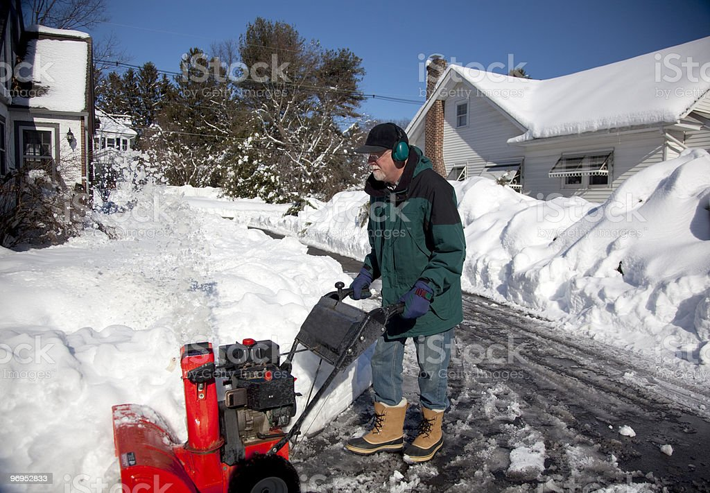 Middle-aged man pushing snow blower royalty-free stock photo
