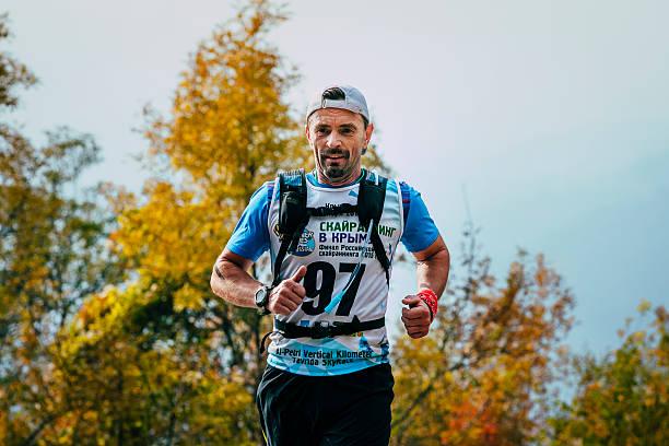 middle-aged man running around  forest with a backpack - jogging hill bildbanksfoton och bilder