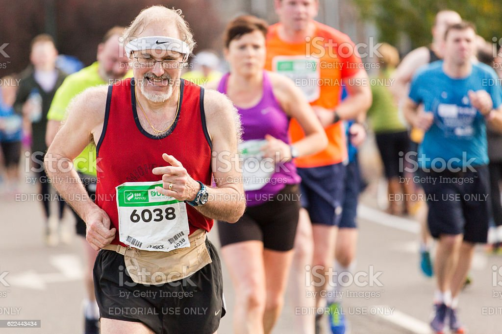 Middle-aged man running marathon stock photo