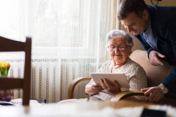middle-aged man showing digital tablet to old lady - 80 89 лет стоковые фото и изображения