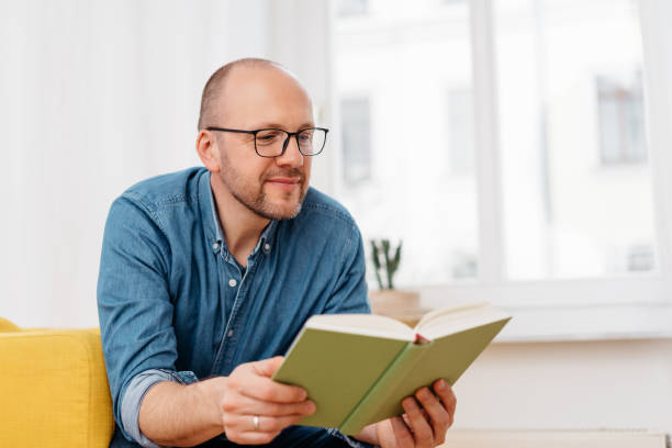 Middle-aged man sitting reading a book stock photo