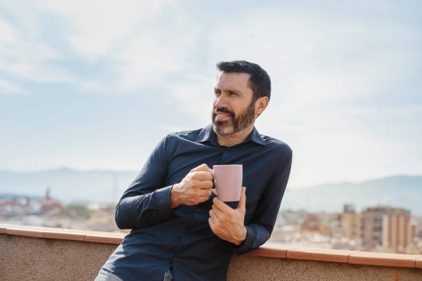 Middle-aged man standing on balcony drinking coffee stock photo
